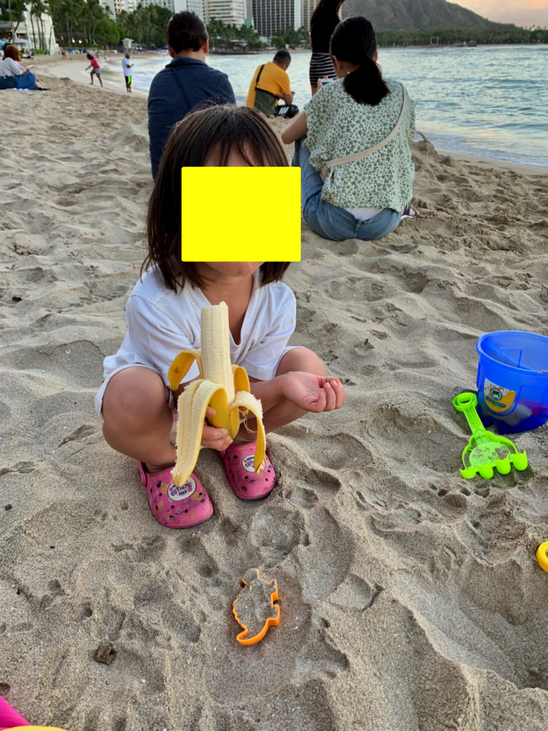 バナナを食べながら砂遊びをする娘。