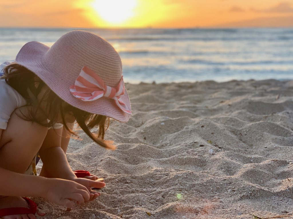 クイーンズビーチで夕日を背景に砂遊びをする娘