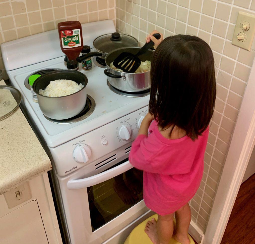 野菜とベーコンを炒める娘