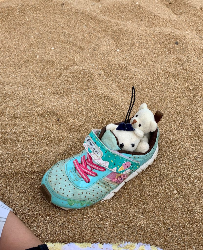砂浜で自分の靴にクマの人形を入れて電車遊びをする様子