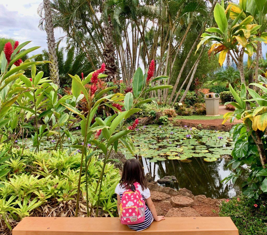 ベンチに座り、池をみる娘 周りには植物が茂っている。