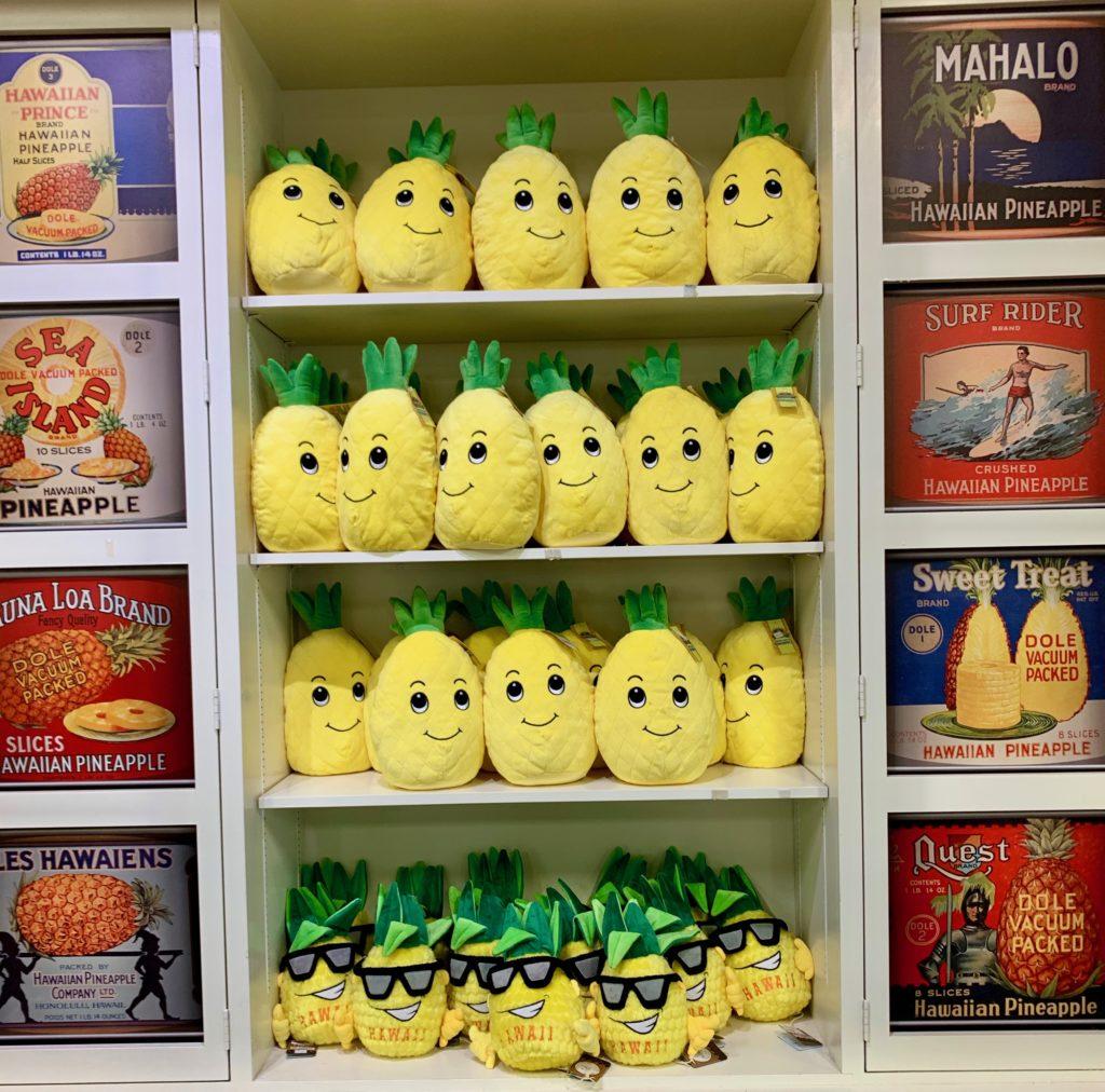 たくさんのパイナップル人形 両端にはパイナップルの広告が並ぶ