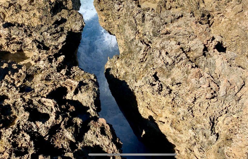 足元に穴があり、穴の底には海水が見える。
