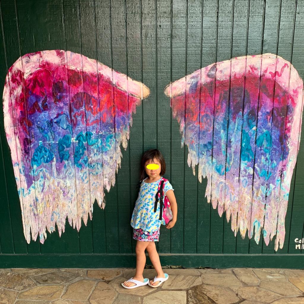 天使の羽のウォールアートの前にたつ娘 羽が頭にあり、届いていない。
