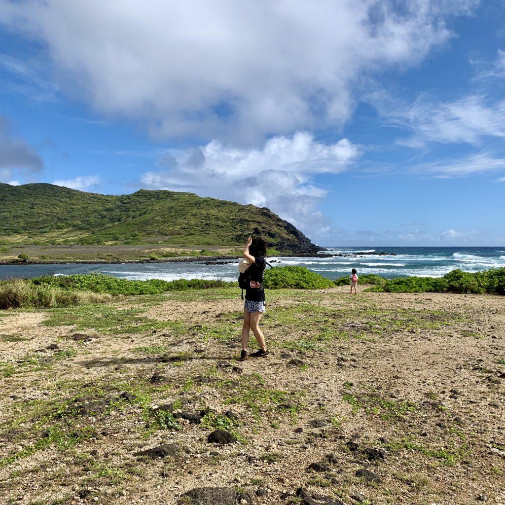 海と山が見えるひらけた場所で休憩する娘と妻