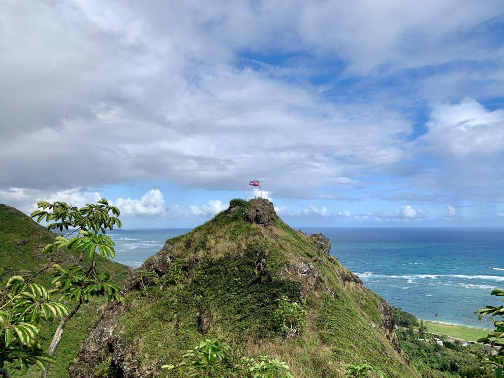 山の頂上にハワイの国旗が刺さっている