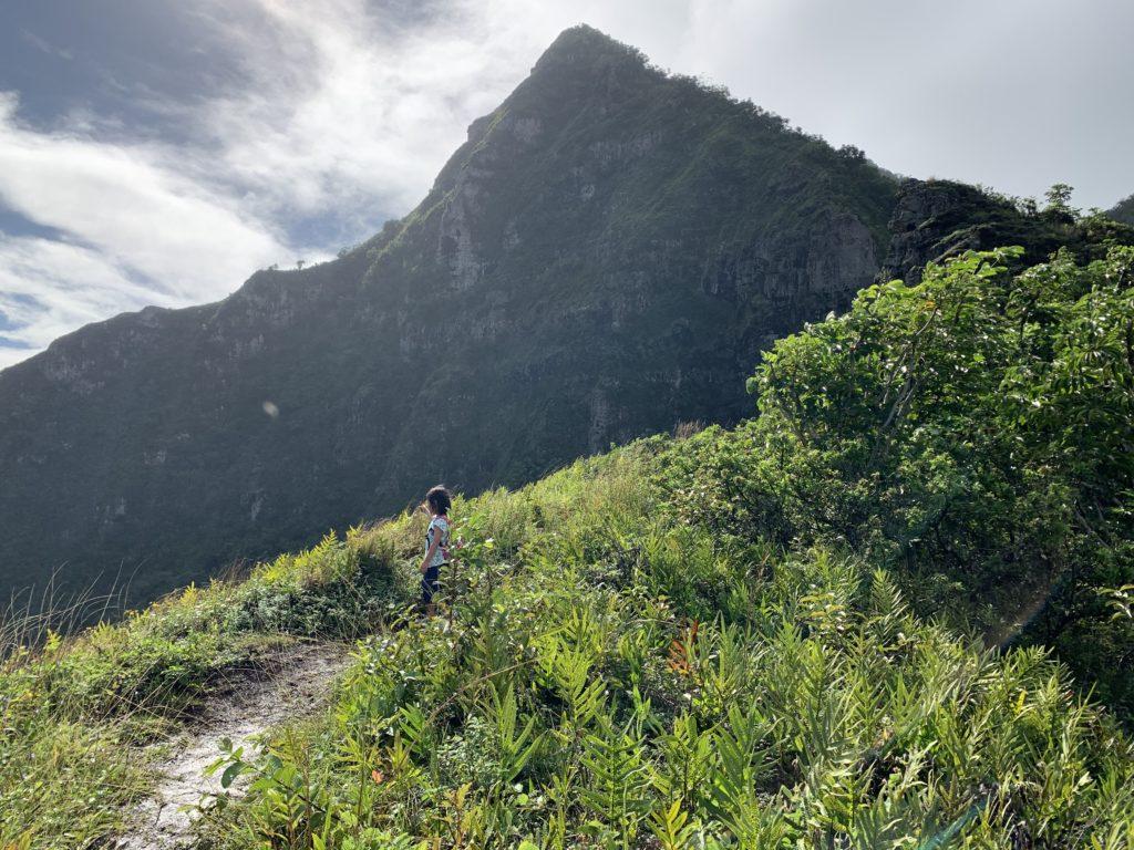 リッジから海を眺める娘 背景にはこれから登る大きな山がそびえている