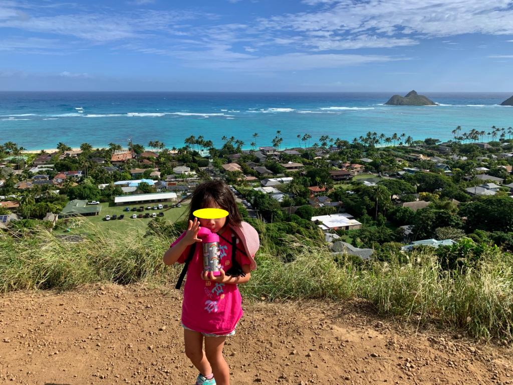 背景にきれいなラニカイビーチが広がる中、水筒の水を飲む娘