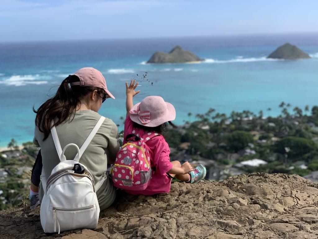 妻の友達と並んで座る娘 砂を崖の下に投げている。 目の前には水色のラニカイビーチが広がる