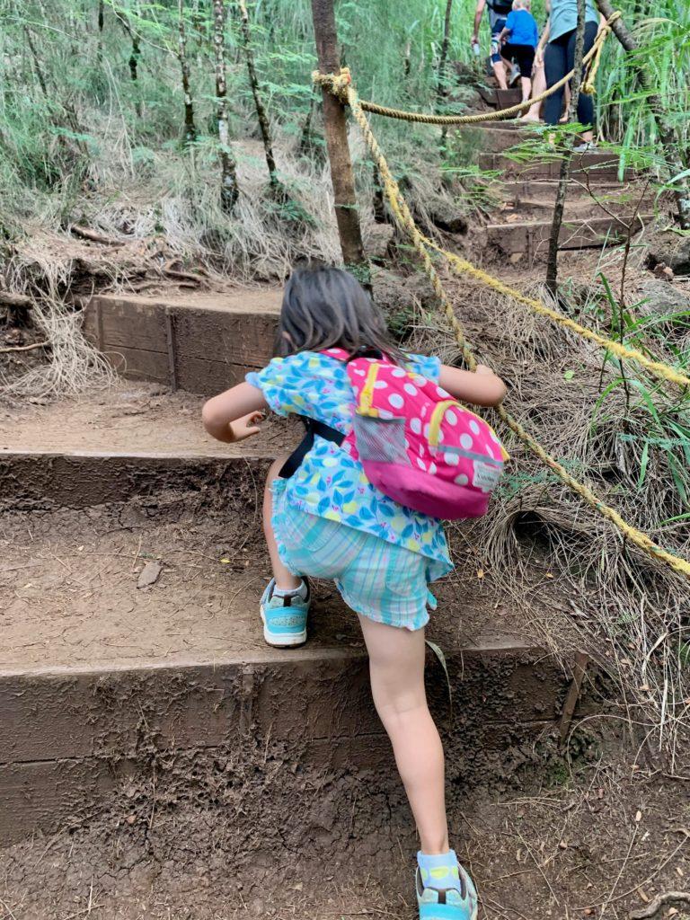 ロープを掴み階段を登る娘