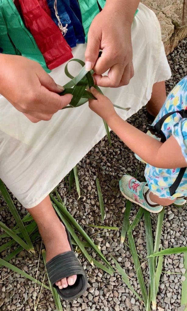 ヤシの葉で魚を作る娘の手