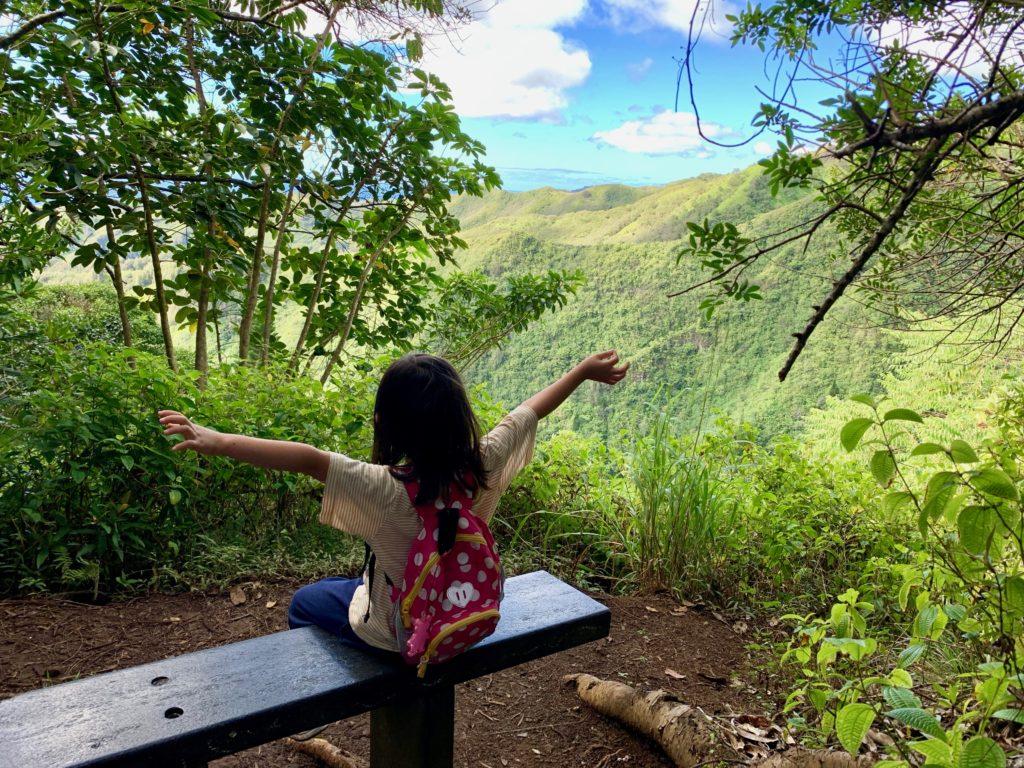 ベンチに座り山を見る娘
