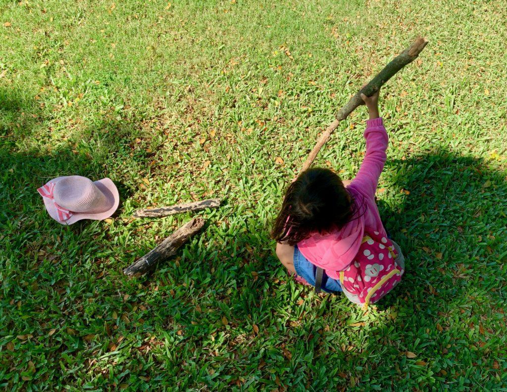 芝生に座り、木の枝4本で遊ぶ娘