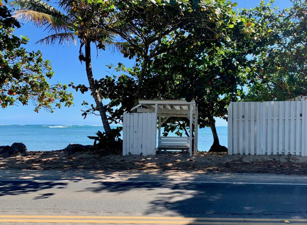 すぐ後ろがビーチになっている白いベンチのバス停