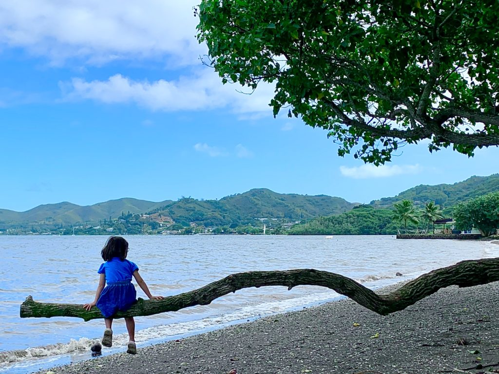 横に伸びる木に座る娘