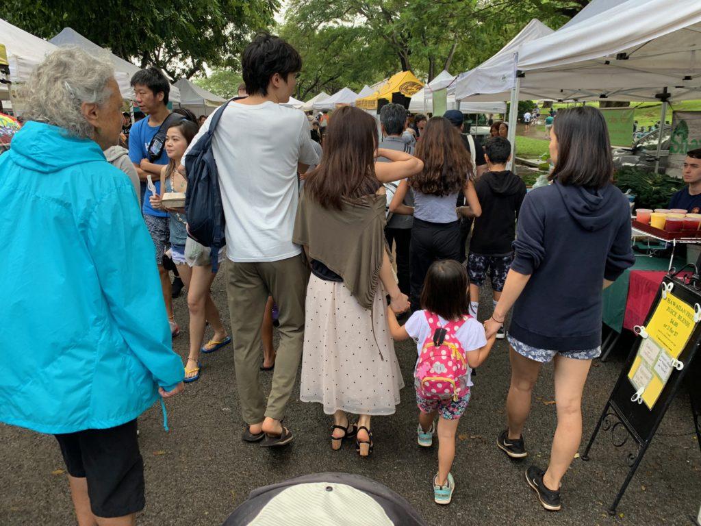 ファーマーズマーケットを歩く友達と家族