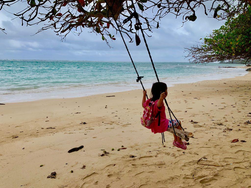 海辺のブランコで遊ぶ娘