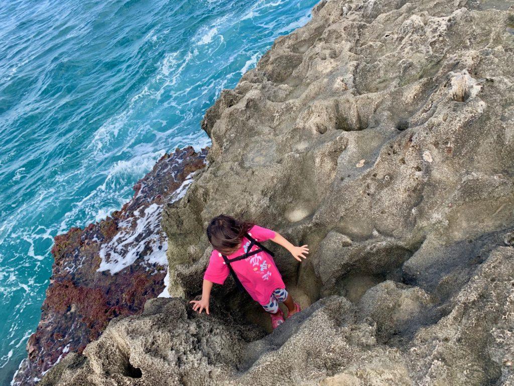 岩のくぼみに入って遊ぶ娘