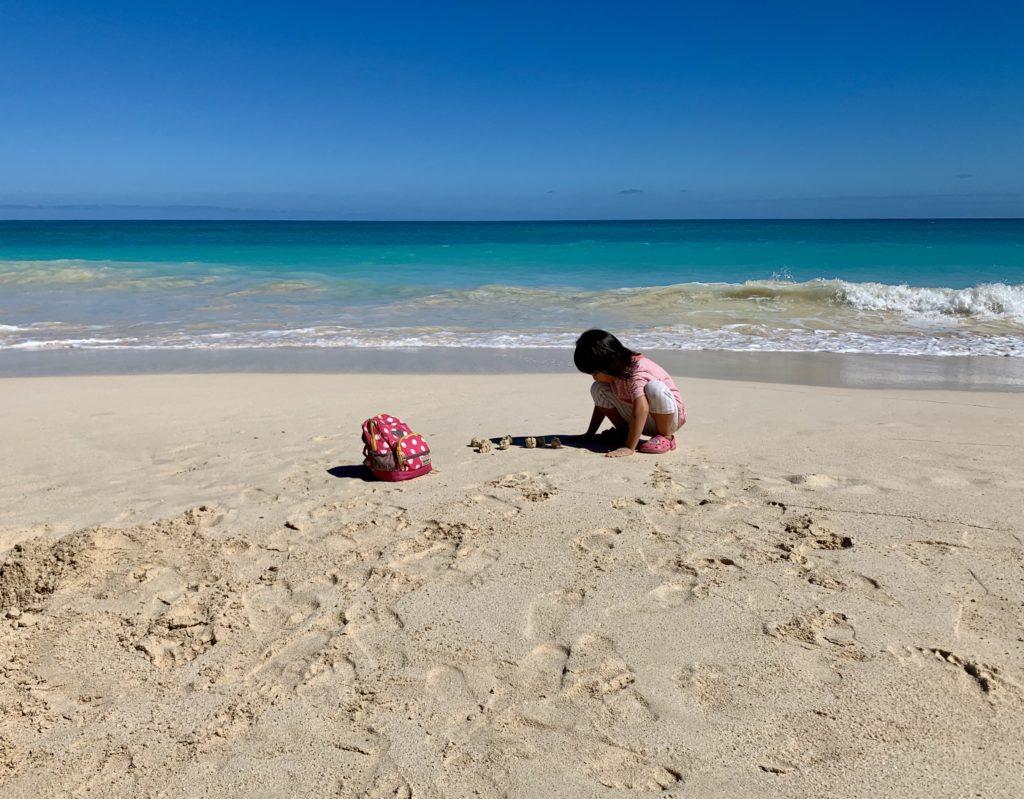 ワイマナロビーチで砂遊びをする娘