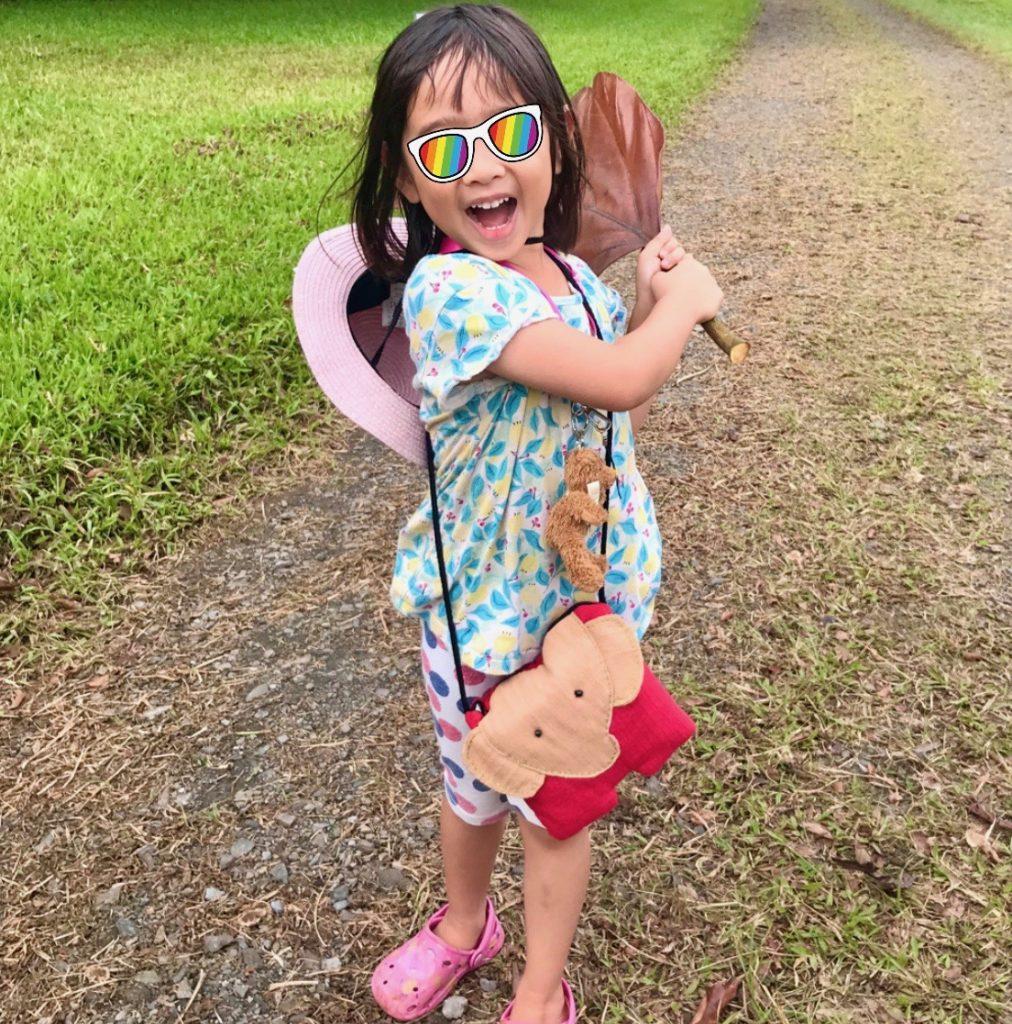 大きな葉を振り回す笑顔の娘