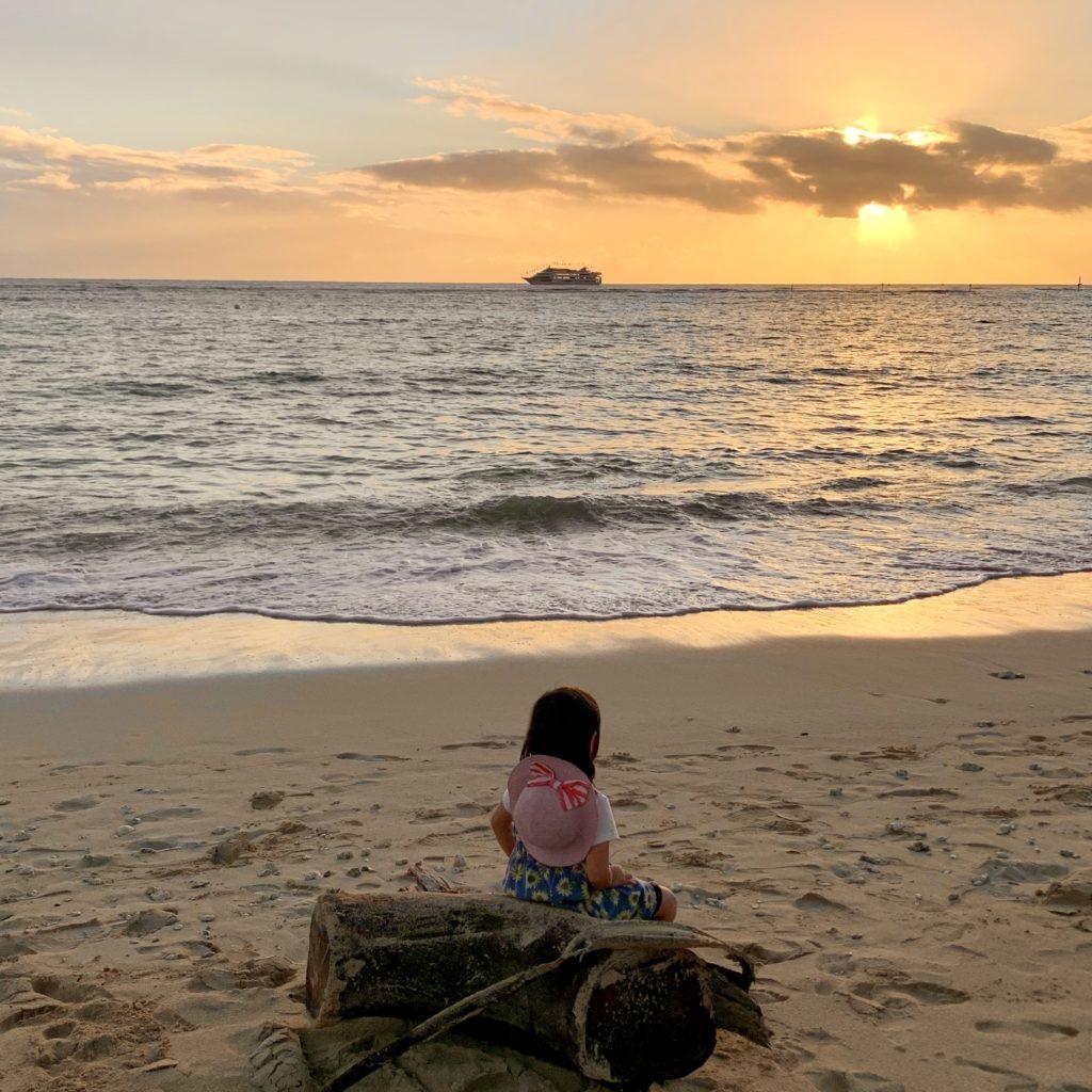 夕日と船と流木に座る娘