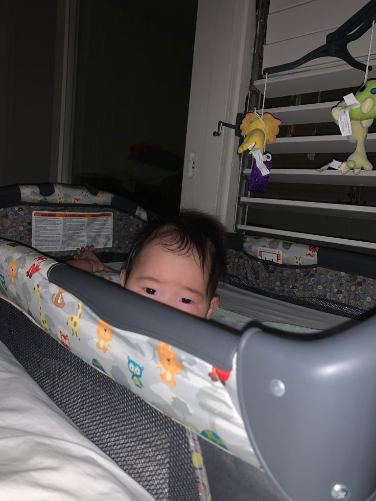 囲いつきベッドの中の息子
