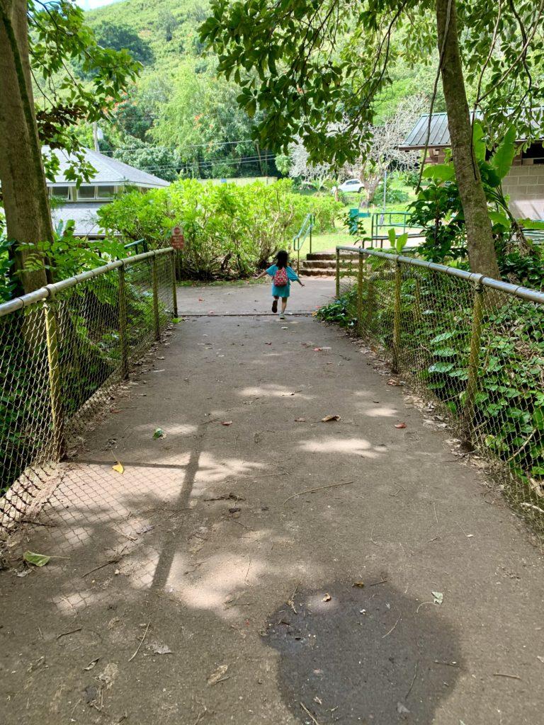 ナアナヘレトレイルの終点の橋を走る娘
