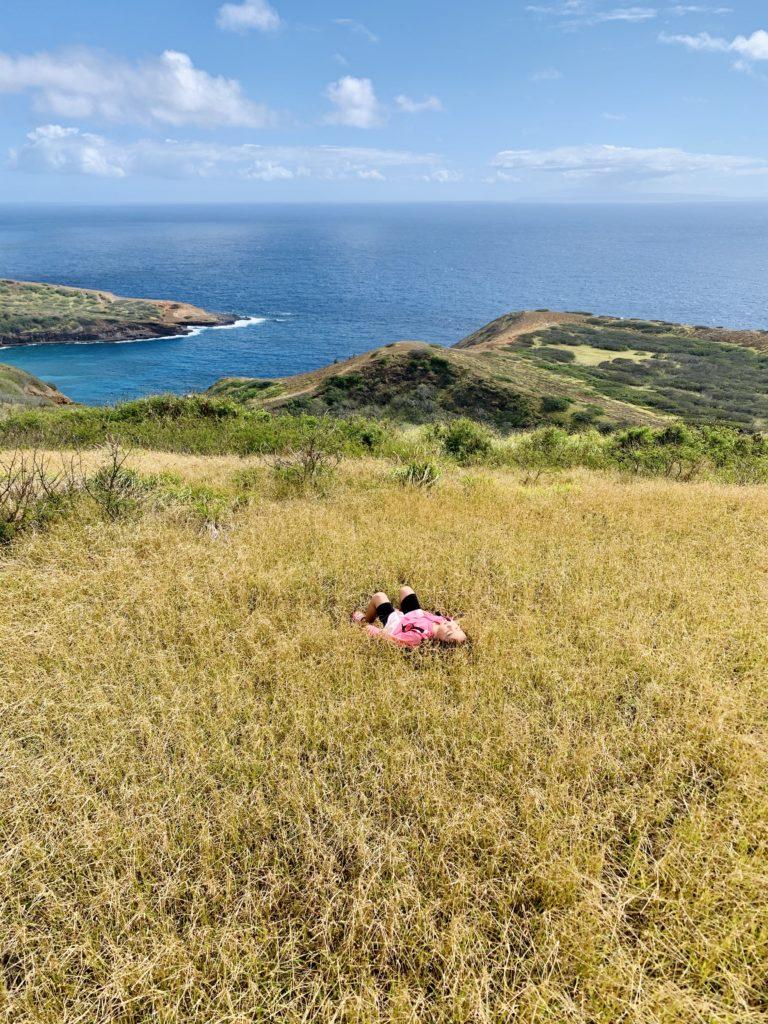 頂上付近の草の中で寝っ転がる娘