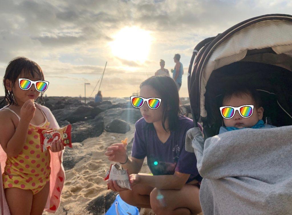 夕日のビーチにいる妻と娘とベビーカーの中の息子