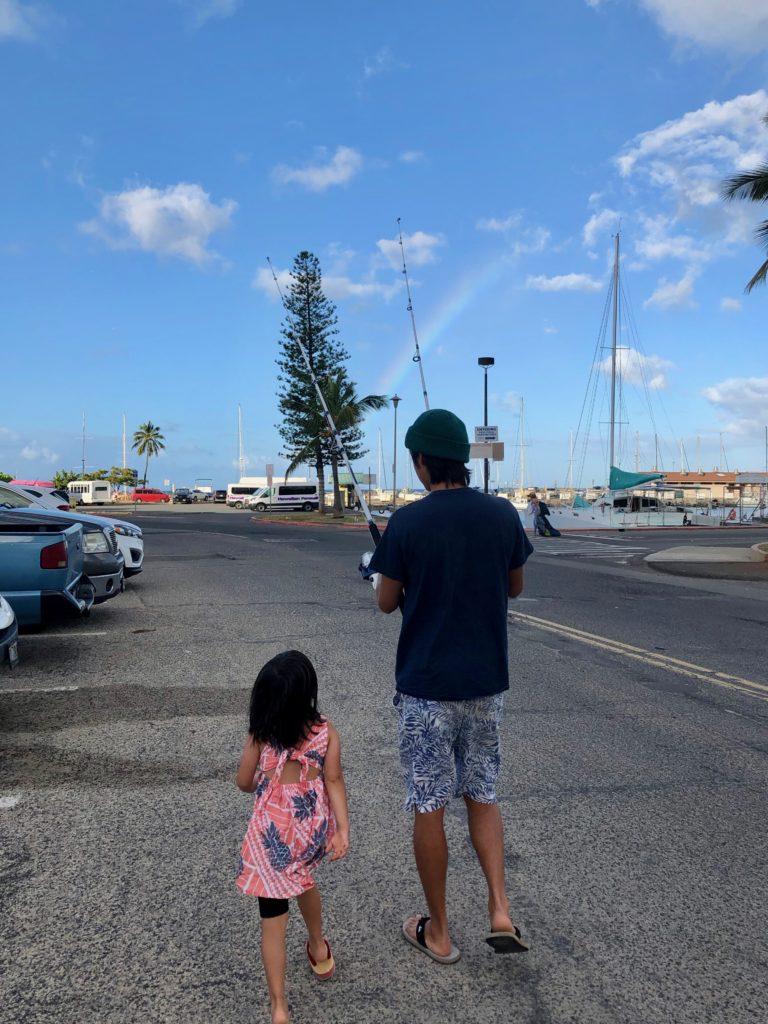 ヒルトンラグーン横の駐車場を歩く私と娘 虹がでている
