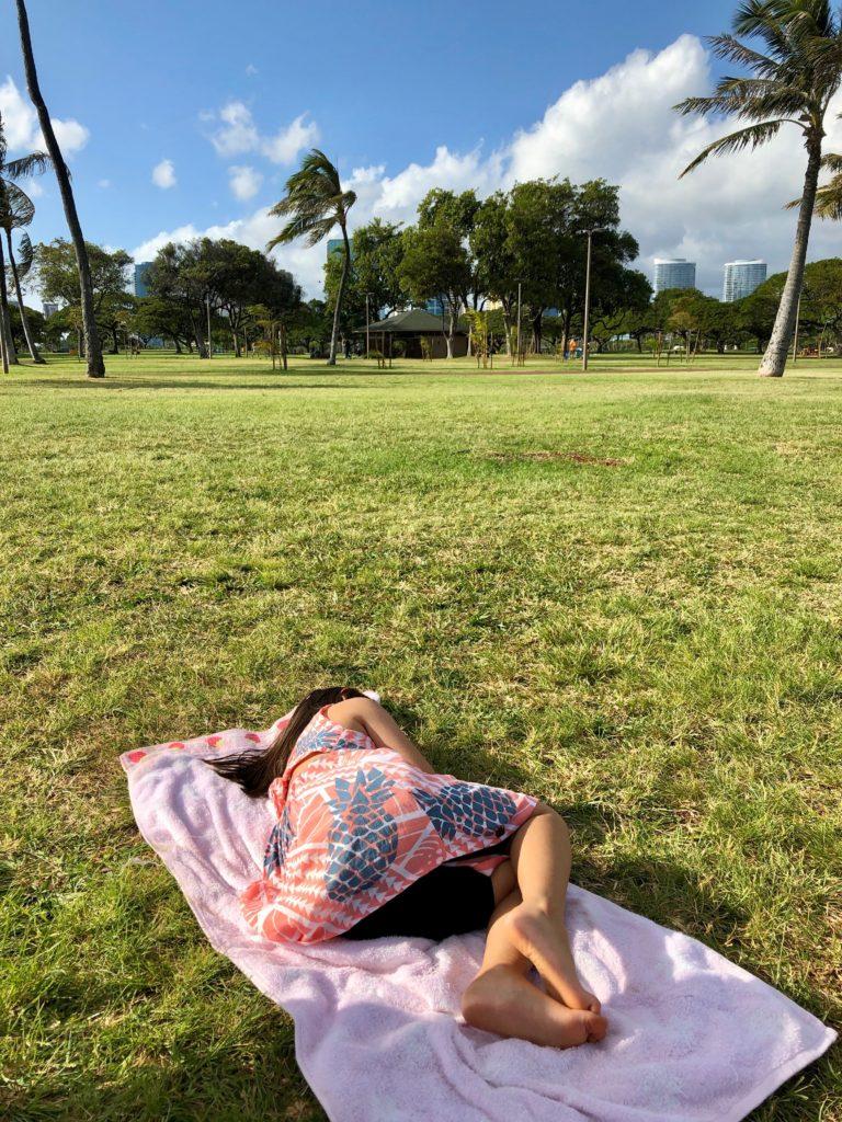 芝生にタオルをしいて寝る娘