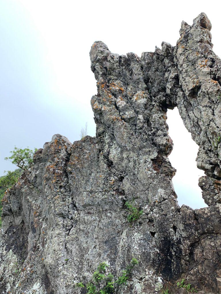 薄くて平たい岩を裏から見ると、大きな穴があいている