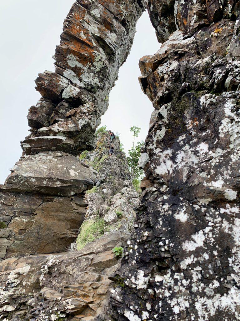 岩に空いた大きな穴から第3ピークを降りる人が見える